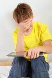 Adolescente triste con la tableta Imagenes de archivo
