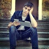 Adolescente triste con la tableta Imágenes de archivo libres de regalías