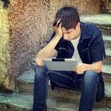 Adolescente triste con la tableta Fotografía de archivo