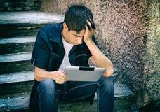 Adolescente triste con la tableta Imagen de archivo