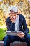 Adolescente triste con la tableta Foto de archivo libre de regalías