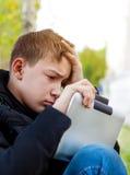 Adolescente triste con la tableta Imagen de archivo libre de regalías