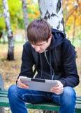 Adolescente triste con la tableta al aire libre Imagen de archivo libre de regalías