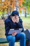 Adolescente triste con la tableta al aire libre Fotos de archivo libres de regalías