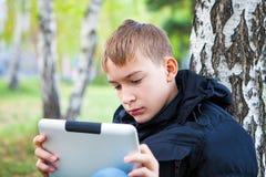 Adolescente triste con la tableta al aire libre Fotografía de archivo libre de regalías