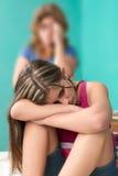 Adolescente triste con su madre preocupante en el fondo Fotos de archivo libres de regalías
