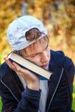 Adolescente triste con un libro Foto de archivo libre de regalías
