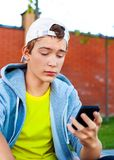 Adolescente triste con un teléfono Imagen de archivo