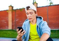 Adolescente triste con un teléfono Fotos de archivo libres de regalías