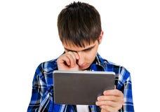 Adolescente triste con una tableta Imagen de archivo libre de regalías