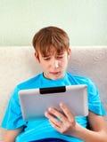 Adolescente triste con una tableta Imágenes de archivo libres de regalías