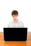 Adolescente triste detrás del ordenador portátil Imagen de archivo
