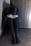 Adolescente triste em um canto fotografia de stock