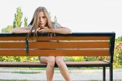 Adolescente triste en banco de parque Imagen de archivo libre de regalías