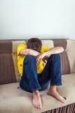 Adolescente triste en el sofá Imagen de archivo libre de regalías