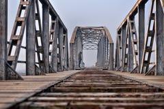 Adolescente triste en la depresión que se sienta en el puente en la puesta del sol Imagen de archivo libre de regalías