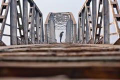 Adolescente triste en la depresión que se sienta en un puente en la puesta del sol Foto de archivo