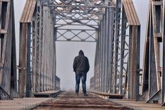 Adolescente triste en la depresión que se sienta en un puente en la puesta del sol Imagenes de archivo