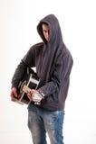 Adolescente triste en la sudadera con capucha que juega a la guitarra acústica Foto de archivo
