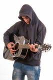 Adolescente triste en la sudadera con capucha que toca la guitarra acústica. El intentar escribir Fotos de archivo