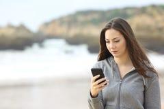 Adolescente triste que comprueba el teléfono móvil Fotos de archivo libres de regalías