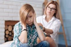 Adolescente triste que cubre sus oídos Imagen de archivo libre de regalías