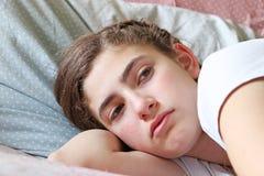 Adolescente triste que miente en cama antes de ir a dormir Imagenes de archivo