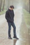Adolescente triste que pone el pie en charco Imagenes de archivo