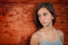 Adolescente triste que se inclina en una pared de ladrillos Foto de archivo