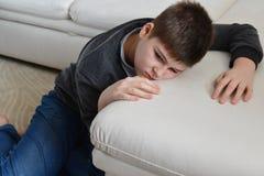 Adolescente triste que se sienta cerca del sofá Fotografía de archivo libre de regalías