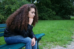 Adolescente triste que se sienta en banco Imagenes de archivo