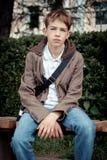 Adolescente triste que se sienta en banco en parque Foto de archivo libre de regalías