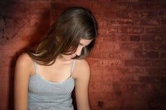 Adolescente triste que se sienta en el piso Foto de archivo libre de regalías