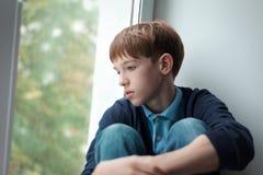 Adolescente triste que se sienta en ventana Imagen de archivo