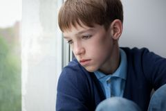 Adolescente triste que se sienta en ventana Foto de archivo libre de regalías