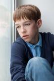 Adolescente triste que se sienta en ventana Fotos de archivo