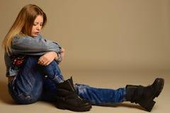 Adolescente triste que senta-se no assoalho das calças de brim, revestimento, sapatas Fotos de Stock Royalty Free