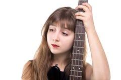 Adolescente triste que sostiene una guitarra, mirando para arriba Imagen de archivo libre de regalías