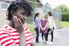 Adolescente triste se sentant gauche par des amis Images stock