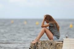 Adolescente triste solamente con el océano en el fondo foto de archivo