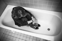 Adolescente triste subrayado que se sienta en baño vacío Fotografía de archivo