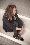 Adolescente triste subrayado que se sienta en baño vacío Imagenes de archivo