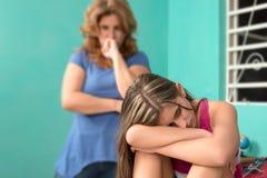 Adolescente triste y su madre preocupante en casa Foto de archivo libre de regalías