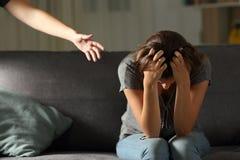 Adolescente triste y una mano amiga en casa en la noche Fotografía de archivo