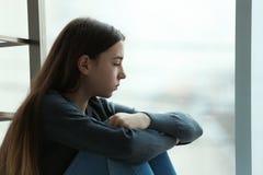 Adolescente turbato che si siede alla finestra all'interno spazio fotografia stock libera da diritti