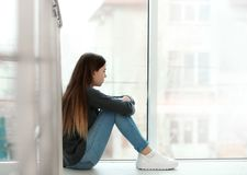Adolescente turbato che si siede alla finestra Spazio per testo fotografia stock