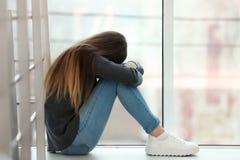 Adolescente turbato che si siede alla finestra Spazio per testo immagini stock libere da diritti