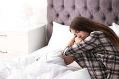 Adolescente turbato che si siede sul letto immagine stock