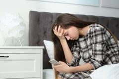 Adolescente turbato con lo smartphone che si siede sul letto fotografie stock libere da diritti