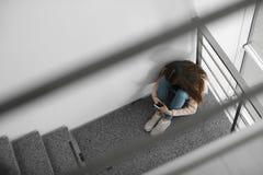 Adolescente turbato con lo smartphone che si siede sulla scala all'interno fotografie stock libere da diritti